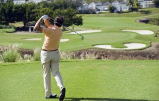 Golfer hits the ball onto the green