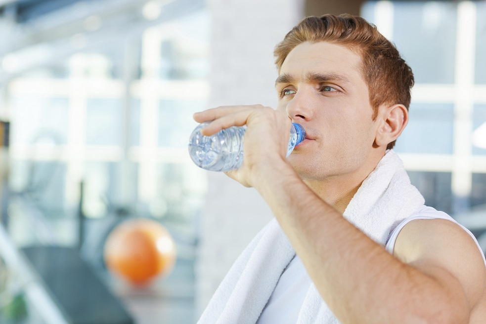 Refreshing after work out. Tired young man carrying towel on shoulders and drinking water while standing in gym