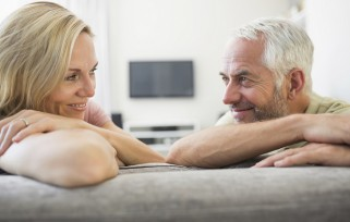 Mature couple on sofa looking at each other  in home