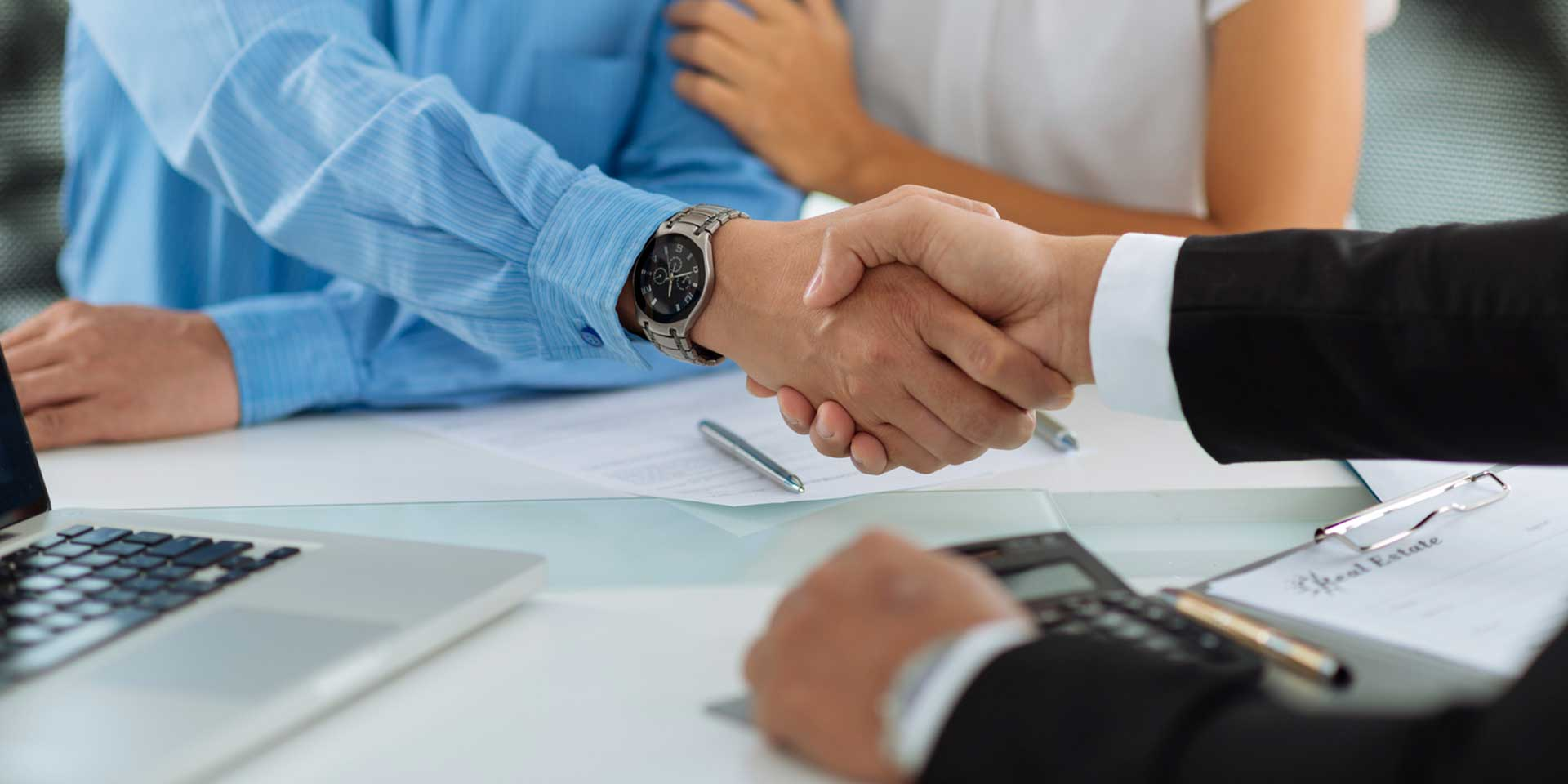 realtor shaking hands with homebuyer.