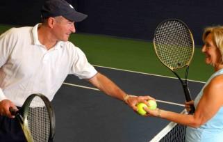 Man and woman holding tennis balls