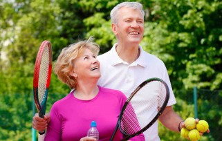 Couple holding tennis rackets.